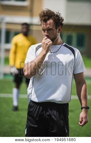 soccer referee whistling in whistle on soccer pitch during game