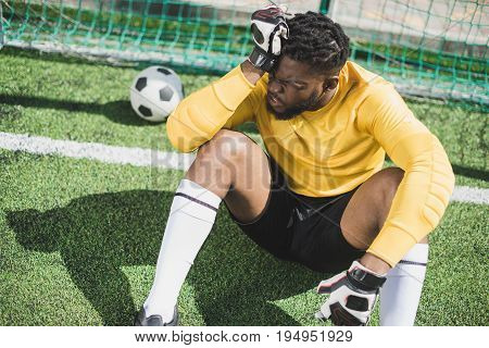 Upset African American Goalkeeper Sitting At Goalpost On Pitch