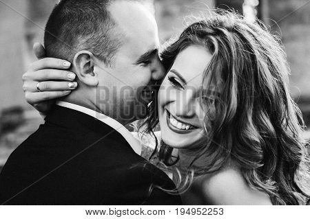 Black And White Photo Of Man Kissing His Laughing Woman