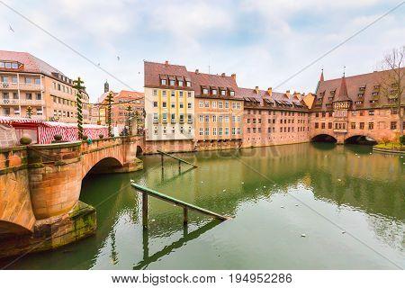 Nuremberg, Germany - December 24, 2016: Old buildings and arch bridge reflected in water in Nuremberg, Bavaria