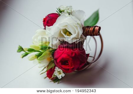 Boutonniere Made Of Dark Rose And White Flower Lies On The Table