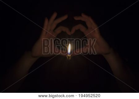 Female hands creating the shape of a love heart Behind a burning candle in complete darkness background