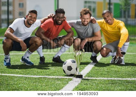 Smiling Multiethnic Soccer Team With Goblet On Soccer Pitch After Game