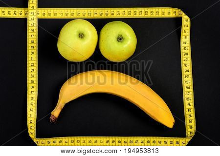 Sad face made of banana fruit and couple of green apples with yellow measuring tape on deep black background. Concept of healthy nutrition food art and emotions