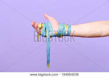 Mans wrist wrapped with cyan and yellow measuring tapes isolated on light purple background. Weight management idea. Hand tied with bicolor flexible rulers. Fitness regime and diet concept