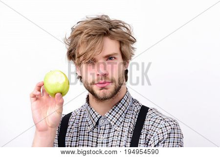 Healthy lifestyle and diet concept. Farmer with fresh fruit isolated on white background. Man with concentrated face beard and stylish hairdo holds green apple in hand. Idea of proper nutrition