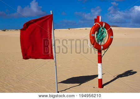 Swimming circle. Life buoy red color on beach with bright sand and sky background. Two warning signs. Safety guard, lifebuoy, lifeguard, life guard. Vacation at ocean.