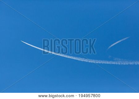 two separating white contrails in blue sky