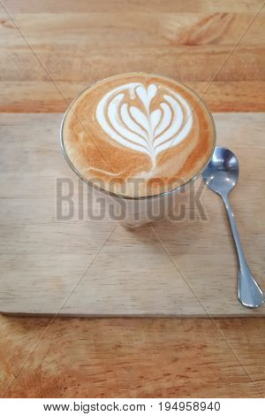 Cup of hot latte art coffee on wooden table background Vintage latte art coffee