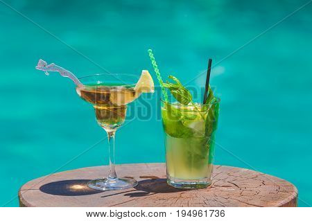 Two cocktails on wooden table next to swimming pool