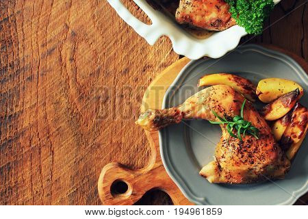 Grilled chicken quarter with potato for garnish. Top view. Wooden background.