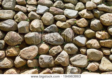 Slope and earth retaining wall made of stone and rocks. Earth material wall abstract texture background