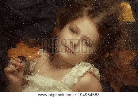 Little caucasian girl, close up portrait  across a water drops on glass, with autumn leaves in background. Emotional portrait, autumn concept.