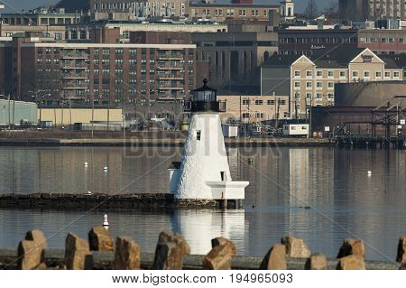 New Bedford Massachusetts USA - April 12 2017: Palmer's Island lighthouse on windless spring morning in New Bedford's inner harbor with hurricane barrier in foreground