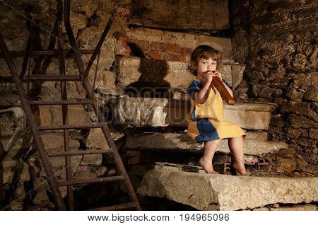 Portrait of pretty little caucasian girl with flute singing on stairs out of an abbandoned antique house