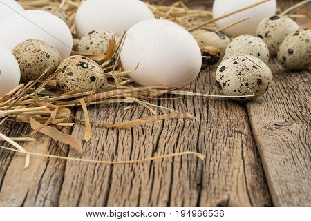 Chicken and quail eggs in a straw and a wooden table. Selective focus.
