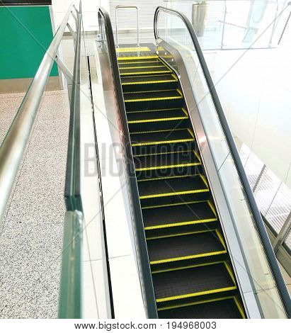 Escalator in an airport; with yellow lines outlining every steps for marking boundary of safety area; installed bollard on top to prevent and stop baggage trolleys.