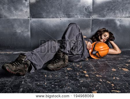 Beautiful tired sexy miner worker in orange helmet with flashlight sitting on a floor on steel background.