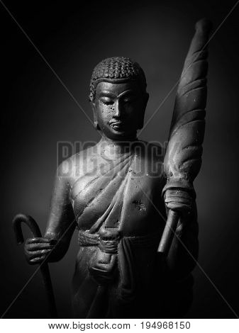 Black and white photo of Buddha statue hold umbrella and stave.