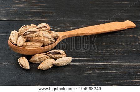 Wild uzbek almonds in a wooden spoon on dark table