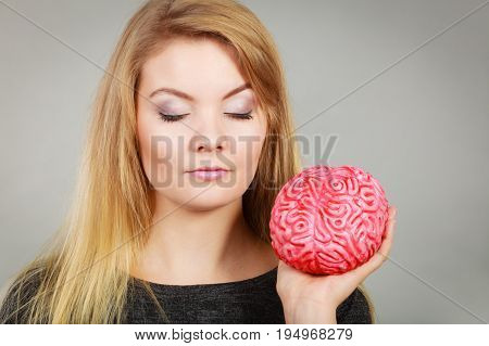 Intellectual expressions being focused concept. Closeup of attractive woman thinking face expression holding brain