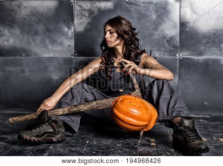Beautiful tired sexy miner worker in orange helmet with flashlight sitting on a floor on steel background. woman holding pickaxe.