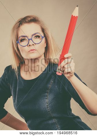 Serious Woman Holds Big Pencil In Hand