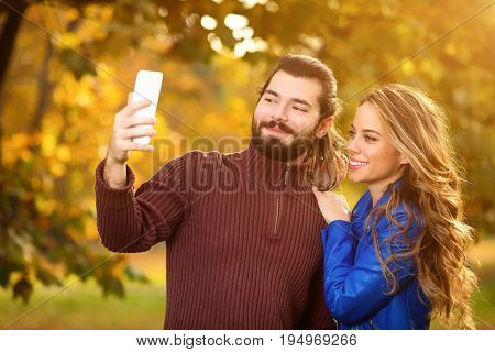 Cute couple using cellphone in the park with autumn / fall colors.