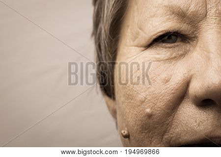 Details of senior woman half face. Elderly pensioner female cheek and eye close up.