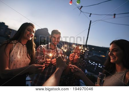 Group of friends enjoying rooftop party with sparklers. Young people enjoying new years eve.