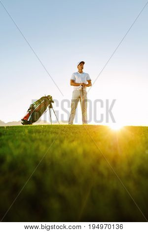Professional Golfer Standing On Field At Sunset