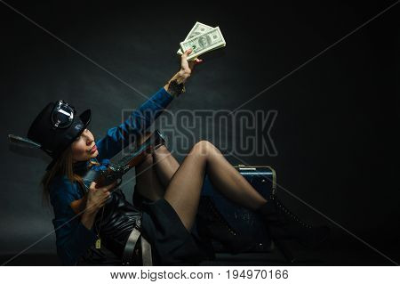Fashionable subculture weapon concept. Steampunk girl with cash. Young gorgeous lady in victorian fashion lying on floor with banknotes briefcase and blunderbuss.