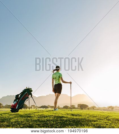 Full length of young woman standing on golf course on a summer day. Rear view of female golfer with golf club on field looking away.