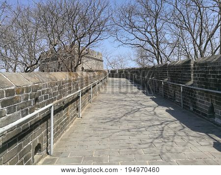China Great Wall with trees in autumn and their shadows on pavement; on Hushan or Tiger mountain, Dandong city, Liaoning province; near China-North Korea border. It is most eastern part of Great Wall. Copy-space for add text is at center-bottom.