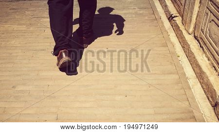 Traveling man walking on an ancient city sidewalk (in China); taken from waist down with shadow of the whole body; retro style; bottom copy space for text