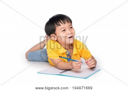 Schoolboy Lying Down And Writing In Notebook.