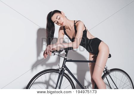 Seductive Young Woman In Black Bodysuit Sitting On Bicycle On Grey