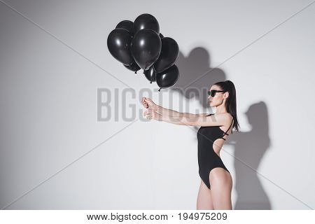 Beautiful Young Brunette Woman In Bodysuit Holding Black Balloons On Grey