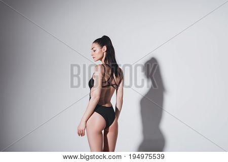 Beautiful Slim Brunette Girl In Black Swimsuit Posing In Studio On Grey