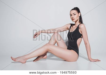 Gorgeous Young Woman In Black Bodysuit Sitting And Looking At Camera