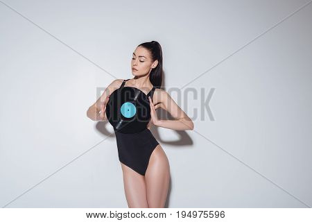 Attractive Young Woman In Black Bodysuit Holding Vinyl Record While Posing In Studio