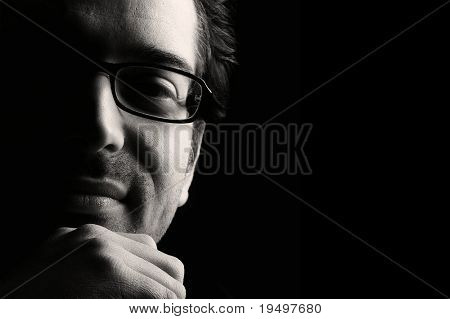 Close-up of young content man resting chin on fist, low key, black and white