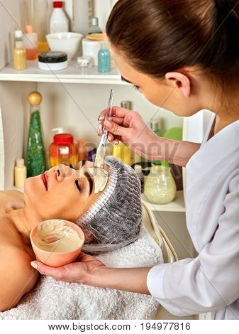 Facial mask and massage for forty five year old woman. Portrait of woman middle-aged take face cleaning by therapeutic mud in European spa salon. Interior cosmetology clinic. Mask against fading skin.