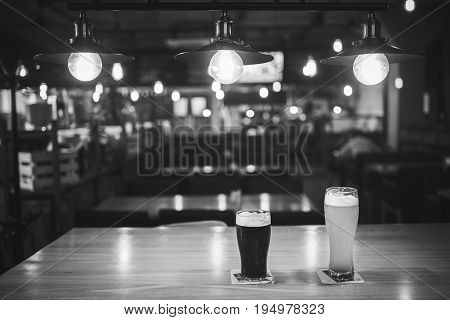 Light and dark beer in glasses on a table in a bar under vintage lamps black and white frame.
