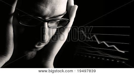 Close-up of thoughtful male professional being worried about poor business outlook, low-key black & white image.