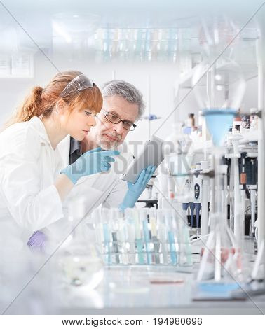 Health care researchers working in life scientific laboratory. Young female research scientist and senior male supervisor looking focused at tablet computer screen evaluating and analyzing study data.