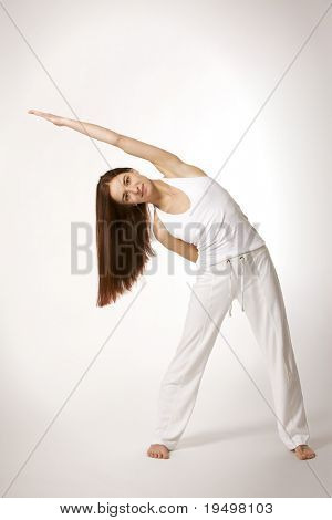 Young lady practicing yoga in triangle posture (Trikonasana) in white clothes on white background, high-key image.