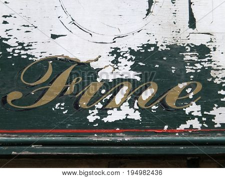 the word fine in hand written script on an old peeling decayed wooden sign