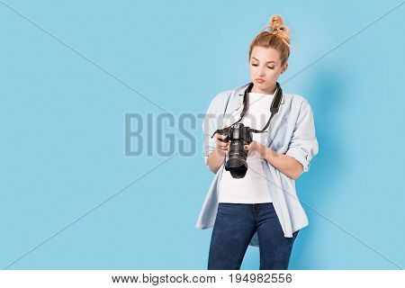 Woman Photographer Is Satisfied About Her Work. Model Isolated On A Blue Background With Copy Space