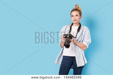 Woman Photographer Is Wondering How To Do Next Photo. Model Isolated On A Blue Background With Copy